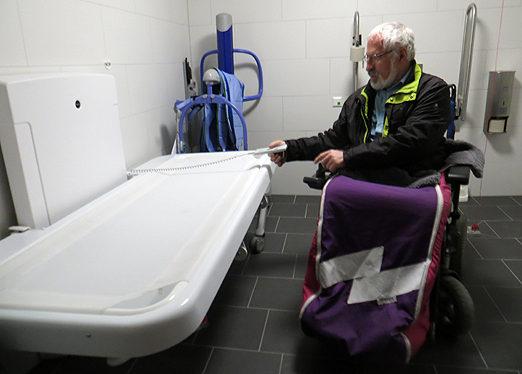 Michael Lutz, einer der beiden Sprecher des Beirats für Menschen mit Behinderungen in Waldkirch begutachtet die neue Toilette und testet die Liege