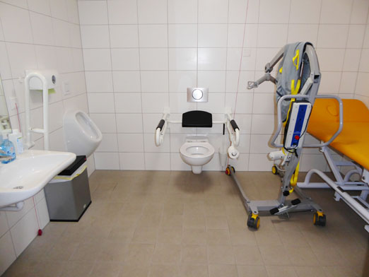 """und so sieht die neue """"Toilette für alle"""" aus! Das Rolli-WC ist zusätzlich ausgestattet mit einer höhenverstellbaren Pflegeliege für Erwachsene und einem mobilen Hebelifter."""